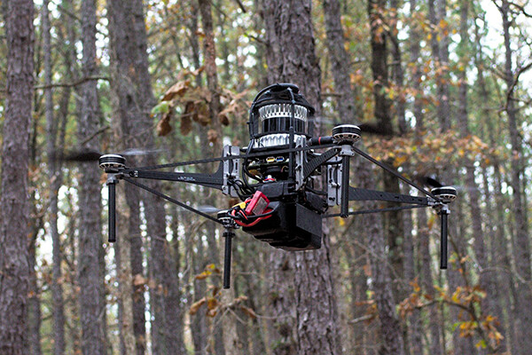 A flying robot flying in a forest in daylight.