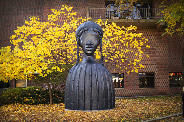Bronze sculpture of a large bust of a Black woman on Penn's campus surrounded by autumn leaves