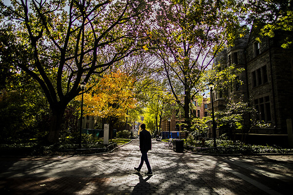 Person walking along Locust Walk at a walkway intersection with colorful autumn leaves.