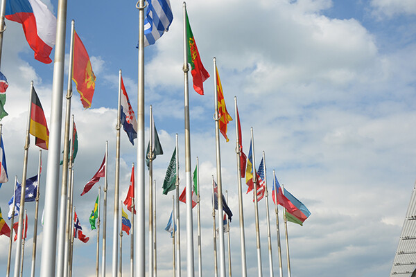 Flags of various nations wave atop flagpoles against a blue sky with clouds