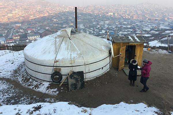 Two people standing beside a Mongolian ger on a hill with Ulaanbaatar in the background.