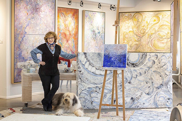 Jill Krutick standing in her studio surrounded by paintings with a fluffy dog at her feet.