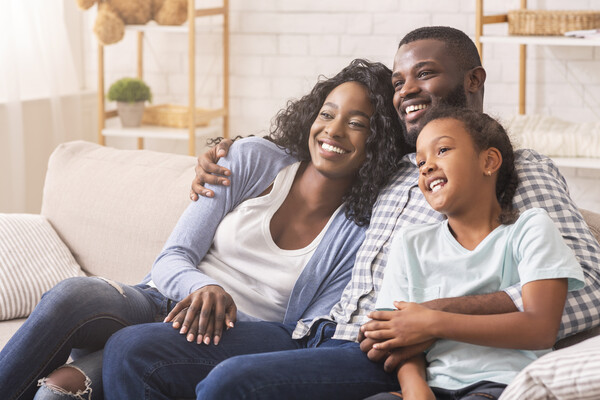 Sitting on a couch embracing and smiling is a Black mom, dad, and daughter.