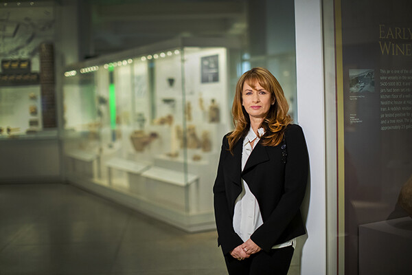 Lynn Meskell standing in front of a glass display case at the Penn Museum.