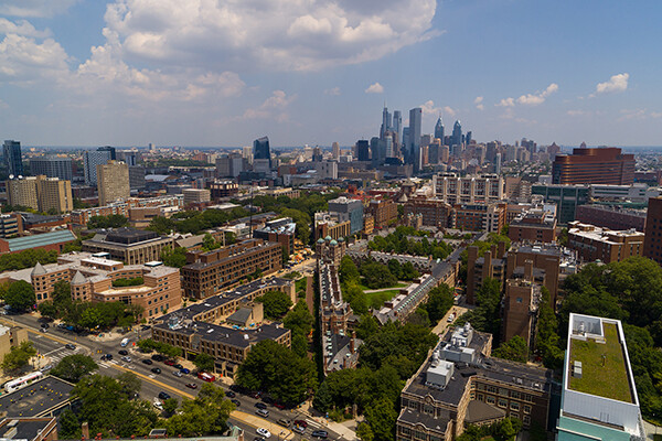 Aerial view of Penn campus and Philadelphia skyline in daylight.