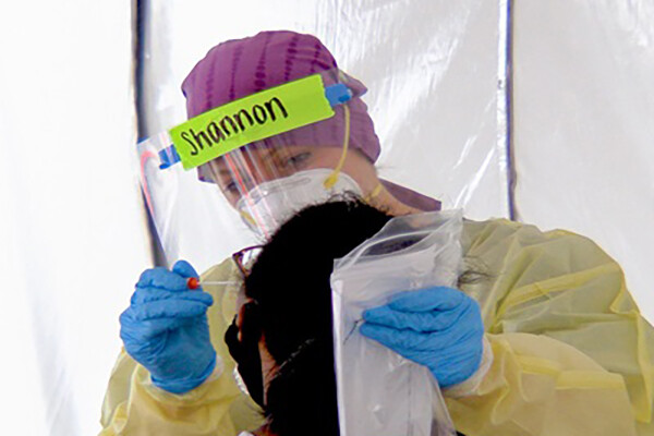 A person in full PPE is administering a COVID nasal swab test.
