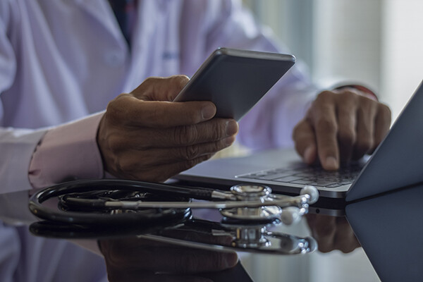 Closeup of doctor's hands holding a smartphone over an open laptop beside a stethoscope.