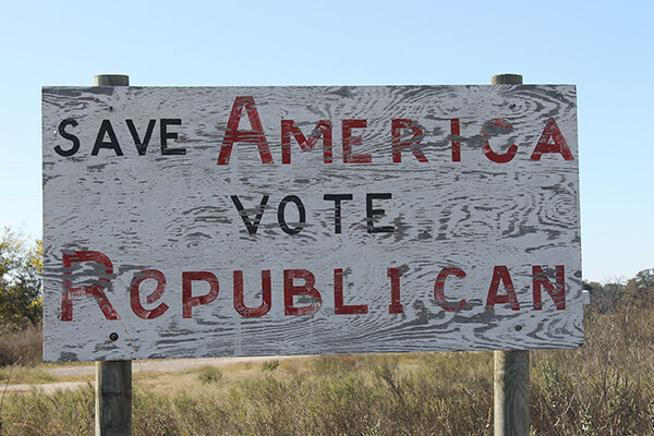 "A faded wooden sign reading ""save America vote Republican"" stands amid scrubby plants on a Texas roadside."