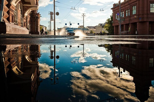 Reflection of a blue sky in a large puddle on a city street with a car driving through wet streets in the sunshine after a rain shower.
