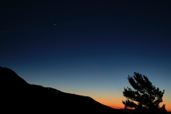 jupiter and saturn visible at dusk just above the horizon of a dark mountain landscape