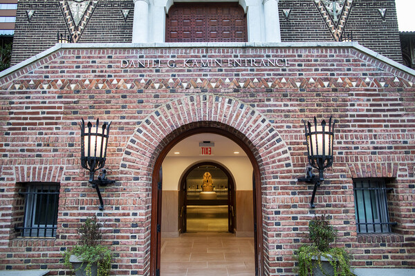 Main entrance of Penn Museum with brick wall and door open showing arched passageway with Sphinx in the doorway in the very back of the view.