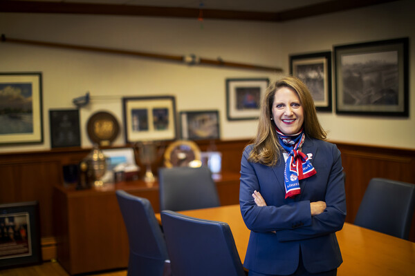 Wearing a Penn scarf, Athletic Director M. Grace Calhoun stands a conference room in front of a long table with chairs.