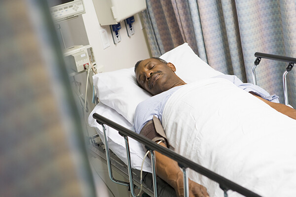African American person lying on a hospital bed asleep.