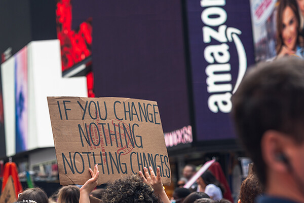 Person in demonstration crowd holding a sign that reads IF YOU CHANGE NOTHING NOTHING CHANGES.
