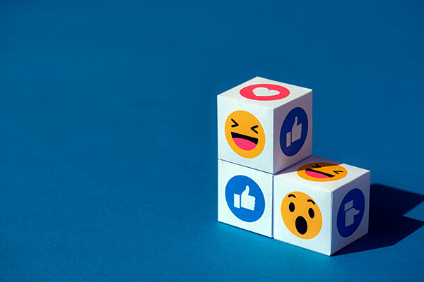 Three cubes with Facebook messenger emojis printed on each side displaying the trademark thumb's up, the laugh emoji and the surprise emoji.