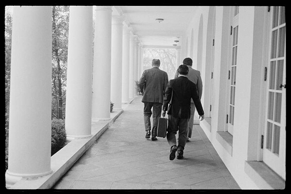 President Gerald Ford and two others are see from behind walking down a White House outdoor walkway in 1975