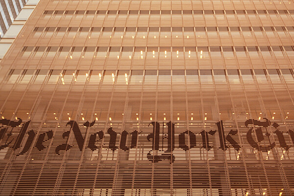 Facade of New York Times building with lettering on the face of the building.