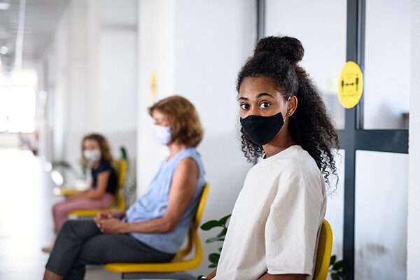 Teenager sitting in waiting room of a clinic wearing a face mask.