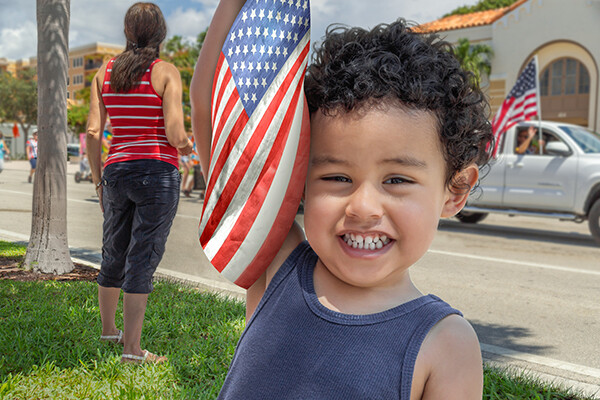 A young child smiles at the camera standing in green grass holding a small American flag next to his head as a pickup truck passes on the street behind him with a passenger waving an American flag.