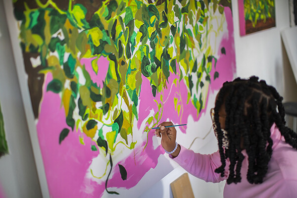 Patricia Renee Thomas paints on a large canvas in her studio.