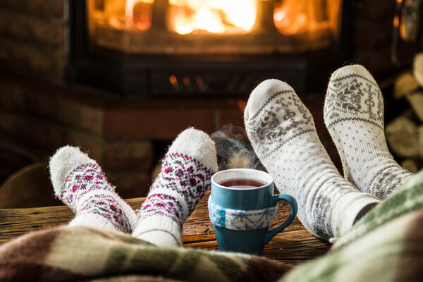 Two pairs of socked feet, up on a bench next to a steaming mug of hot liquid. In the background is a fireplace with a fire.