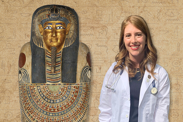 Charlotte Tisch wearing a white medical coat and stethoscope standing next to a fresco of a mummy.