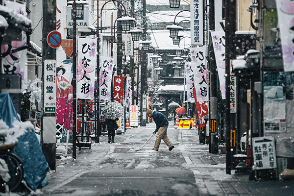 Man shovels snowy street, which is lined by lanterns and banners with Japanese characters