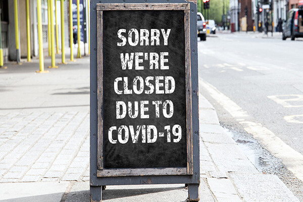 Sandwich board on a city sidewalk that reads SORRY WE'RE CLOSED DUE TO COVID-19.