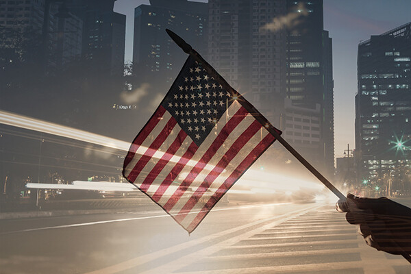 A hand is seen waving a small American flag as traffic zips by on a city street at dusk
