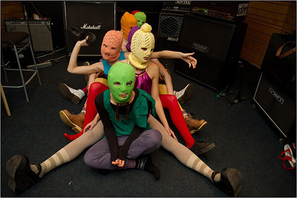 Group of women wearing colorful knitted balaclavas sit on the floor in front of Marshall speakers and amps
