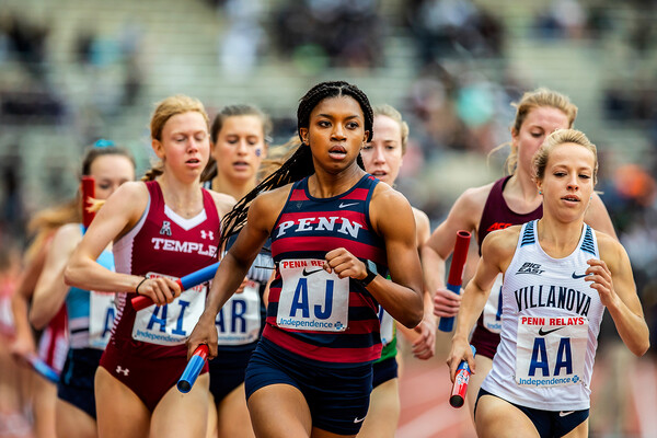 Nia Akins leads a pack of runners while running in a relay race at the Penn Relays.