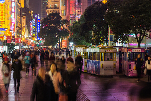 Busy sidewalk in urban China at night with crowds walking past commercial businesses.