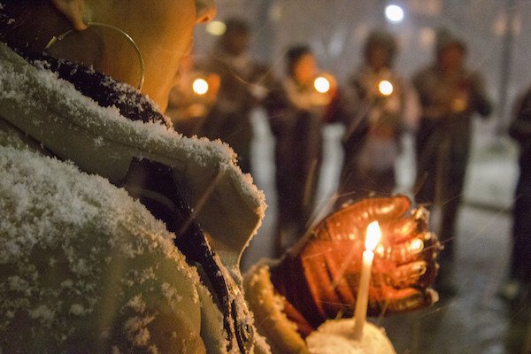 Woman cups a candle with a gloved hand. She is standing in a circle with other candle-holders in the snow.