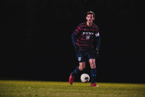 While playing against Princeton, Penn's Alex Touche kicks the ball up the field.