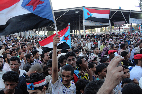 Large group of men gather in the street in Yemen holding the country's flag during the 2011 Arab Spring.
