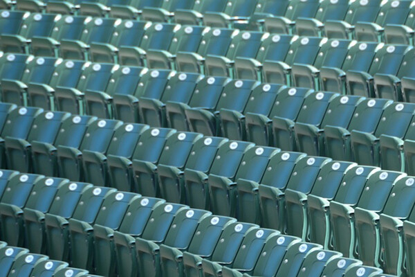 Empty stadium seats indicating no spectators at a sporting event.