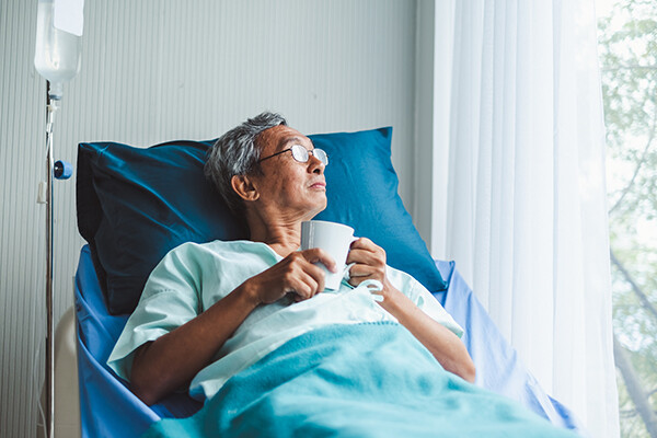 Recovering hospital patient sitting up in hospital bed holding a cup of tea looking out the window.