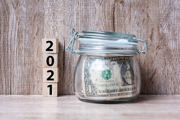 picture of savings jar with money in it and blocks saying 2021