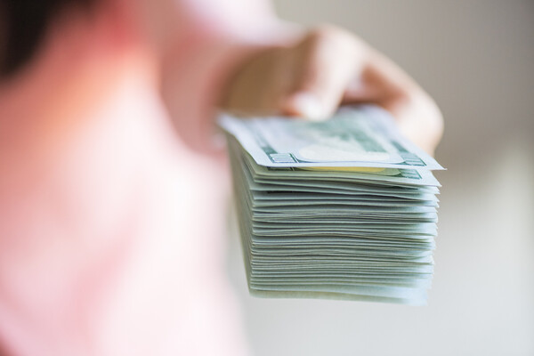 A blurred hand holding a stack of dollar bills, pushing them toward the camera.