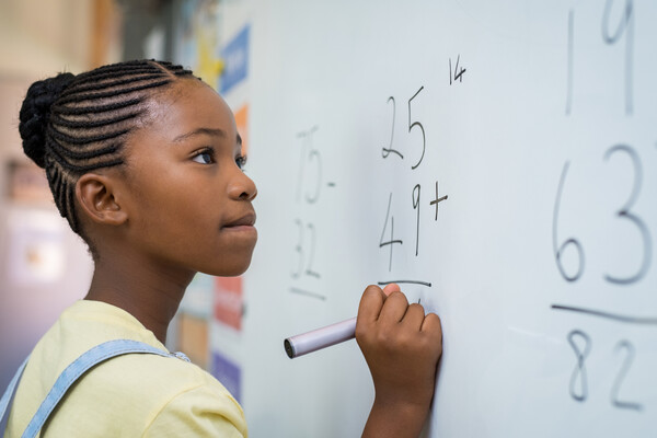 A young girl doing a math problem at a whiteboard. The numbers 25, 49, and 14 are visible.