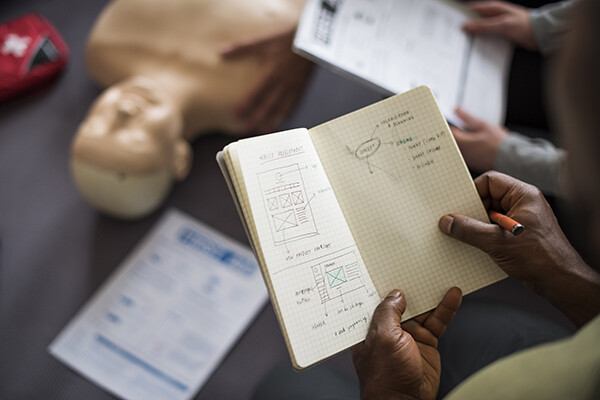 Person holding a sketchbook over a table with a human anatomy dummy.