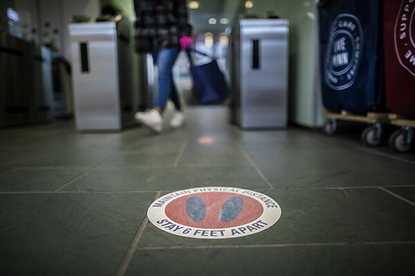 Floor decal that reads MAINTAIN SOCIAL DISTANCE STAY 6 FEET APART on the floor of a campus building at Penn.