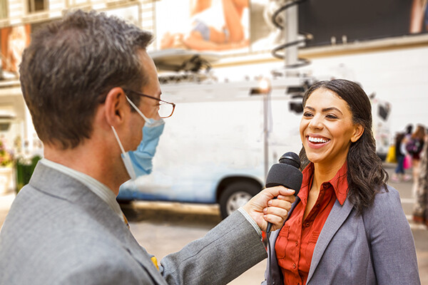 Masked news reporter holds a microphone to an interviewee laughing and responding.