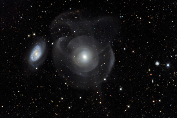 rendering of the elliptical galaxy NGC 474 and spiral galaxy 470 with star shells