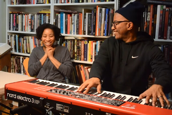 Father plays keyboard while his daughter smiles. Bookshelves in background.