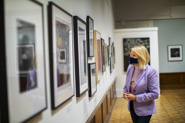 Curator standing in gallery looking at artworks on a wall