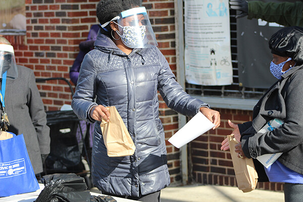 Person standing outside holding a brown lunch bag to distribute wearing a face shield and mask outside a building in West Philadelphia