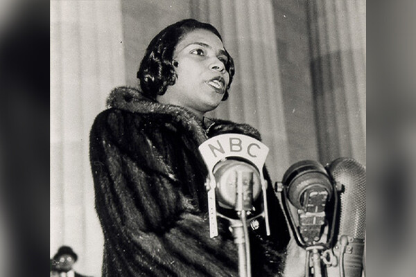 Woman in a fur coat sings before several microphones; one says 'NBC'
