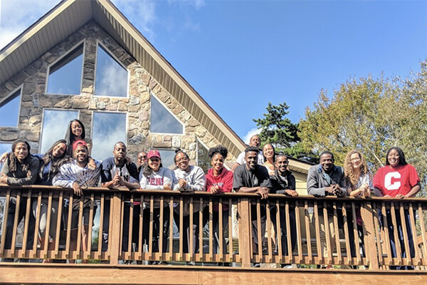 Group of BLSA students standing by a railing on an outdoor porch in the sunshine.