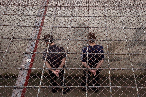 Two incarcerated people seen from above and behind with their hands handcuffed behind their backs outside in a prison yard.